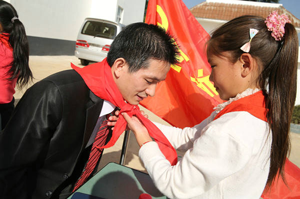 西昌巴黎人彩票希望小学学生给梁汉桥老师系红领巾